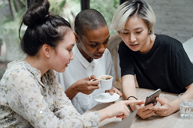 3 women looking at a phone over coffee